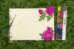 Handmade sketchbook with flowers and leaves of wild rose. Watercolor paints and brush on the background of grass Stock Images