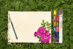 Handmade sketchbook with flowers and leaves of wild rose. Watercolor paints and brush on the background of grass Royalty Free Stock Photography