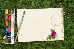 Handmade sketchbook with flowers and leaves of wild rose. Watercolor paints and brush on the background of grass Stock Photo