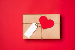 Handmade small gift box with heart symbol on red background. Royalty Free Stock Photo
