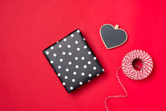 Handmade small gift box with heart symbol on red background. Stock Photos