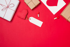 Handmade small gift box with heart symbol on red background. Stock Image