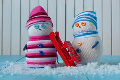 Handmade snowman, snowmen stay with red sled on Royalty Free Stock Image