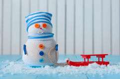 Handmade snowman stay with red sled on light Stock Image