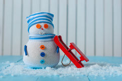 Handmade snowman in striped cap with red sled on Stock Image