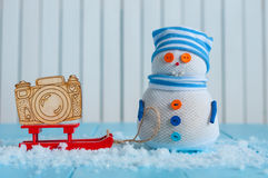 Handmade snowman in striped cap with red sled and Royalty Free Stock Images