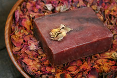Handmade Soap. Handmade herbal soap bar in a bowl of aromatic dried rose petals royalty free stock photo