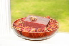 Handmade Soap. Handmade herbal soap bar in a bowl of aromatic dried rose petals royalty free stock photography