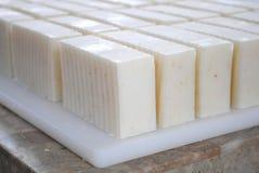 Handmade Soap Bars Batch. Batch of handmade oatmeal soap bars wavvy cut bars on a cutting board stock photo