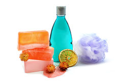 Handmade soap, blue colored shower gel bottle and soft bath puff or sponge. Stock Photo