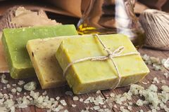 Collection of handmade, natural organic soap and cosmetic oil on wooden background. Spa products. Purple and vintage tinted royalty free stock images