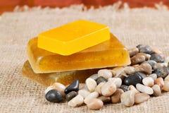 Handmade soap and sea pebbles. Bars of handmade soap and sea pebbles on mat Royalty Free Stock Image