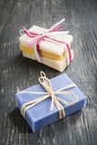 Handmade soaps. Colorful handmade soaps tied with strings on rustic wooden background Stock Photo