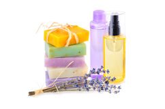 Handmade soaps and lotions. Handmade herbal soaps with lavender flowers and group of lotions in bottles on white background Royalty Free Stock Photo