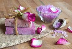 Handmade soaps and sea salt. Rose handmade soaps and sea salt on wood royalty free stock photography