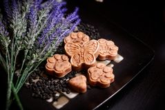 Handmade sopas on plate with flowers. Five natural, handmade soaps lies on black plate with flowers. They are in many shapes such as a butterfly, a paw royalty free stock photography