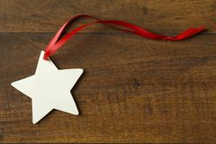 Handmade, star-shaped blank Christmas holiday gift tag with red ribbon decorations on rustic wood background Royalty Free Stock Photo