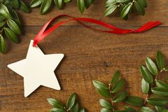 Handmade, star-shaped blank Christmas gift tag with red ribbon and natural evergreen decorations on rustic wood background Stock Images