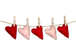 Handmade stitched hearts on a line. Five handmade stitched felt hearts hanging on a clothes line, pink and red isolated on a white background Royalty Free Stock Photos