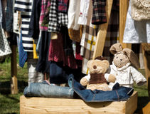 Handmade stuffed toys in wooden box at yard sale. Clothes on racks in background. Craft concept. Text space stock photography