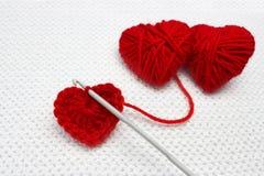 Handmade szydełkujący wełny organicznie czerwony serce Stara metalu szydełkowania haczyka i dwa czerwieni przędzy piłka jak serce Fotografia Royalty Free