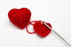 Handmade szydełkujący wełny organicznie czerwony serce Stary metalu szydełkowania haczyk i czerwona przędzy piłka jak serce na bi Obraz Stock