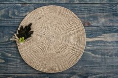 Handmade Table Mat of Jute Rope Twisted in a Spiral Form. On blue wooden background Stock Photos