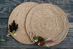 Handmade Table Mat of Jute Rope Twisted in a Spiral Form. On blue wooden background Royalty Free Stock Image