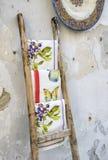Handmade tablecloths, on wooden ladder. Stock Photo