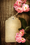Handmade tag with robin hood roses. On a rustic wooden table Royalty Free Stock Photos
