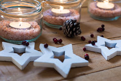 Handmade tea lights in jars with salt, wood stars, pine cone and red berries Christmas, New Year, advent Stock Image