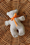 A handmade teddy bear with an orange ribbon on a straw mat. Toys for babies. Stock Photo