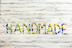 Handmade. Text written in beads on a wooden background Royalty Free Stock Photography