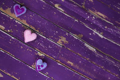 Handmade textile felt toy hearts on old violet wooden floor. Handmade textile felt toy hearts - violet, pink with beads - on old wooden floor Royalty Free Stock Image