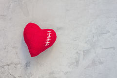 Handmade textile heart was broken and sewed again with white thread on a gray concrete background Royalty Free Stock Image