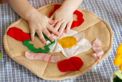 Handmade textile toy pizza and child's hands Stock Photography