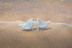 Handmade toy birds with wedding rings on the beach Stock Photography