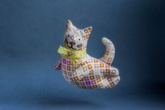 Flying reddish-brown cat. Handmade toy with a bow around his neck. From a cloth with a pattern, soft. Kind, pleasant, smiling cat Royalty Free Stock Photos