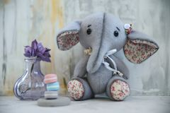 Handmade toy gray elephant with purple flower. Handmade retro toy gray colourful elephant with foam eva purple flower handcrafted plush doll furry toy cute Stock Images