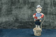 Handmade toy sailor boy figure in vest lifebuoy. Handmade toy sailor little boy cheeks figure in blue white vest paper hat and shorts with red lifebuoy retro Stock Images