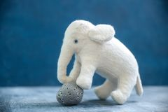 Handmade toy white elephant with gray stone. Handmade retro toy white elephant with gray stone handcrafted plush doll furry toy cute adorable with blue eyes Stock Photos