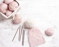 Handmade trykotowy różowy kapelusz z z futerkowym pomponem na drewnianym stole Zdjęcie Royalty Free