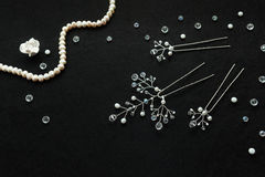 Handmade wedding jewelry and pearls on the the black background. Handmade white gentle wedding bijouterie: hairpins with crystals branches decoration and white Royalty Free Stock Image