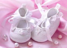 Handmade white baby booties. With pearls stock images