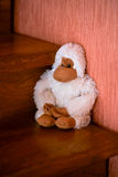 Handmade white monkey toy seating on the brown wood stairs Royalty Free Stock Photos