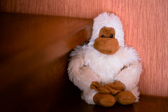 Handmade white monkey toy seating on the brown wood stairs Royalty Free Stock Images