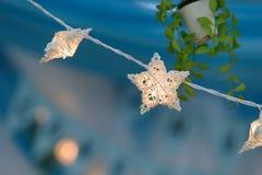 Handmade white wicker star with light bulb Stock Photos