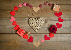 The handmade wicker heart and many hearts around Stock Images