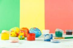 Handmade Wielkanocni jajka na multicolor drewnianym tle z farbami i muśnięciem obrazy stock