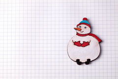 Handmade wood christmas decoration snowman on squared paper Royalty Free Stock Photos